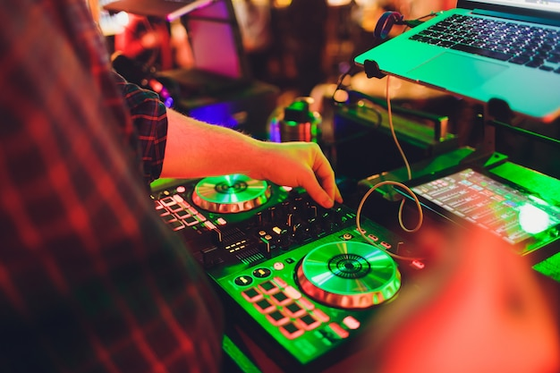 Hands of dj mix tracks on digital turntable and software on laptop with professional mixing software