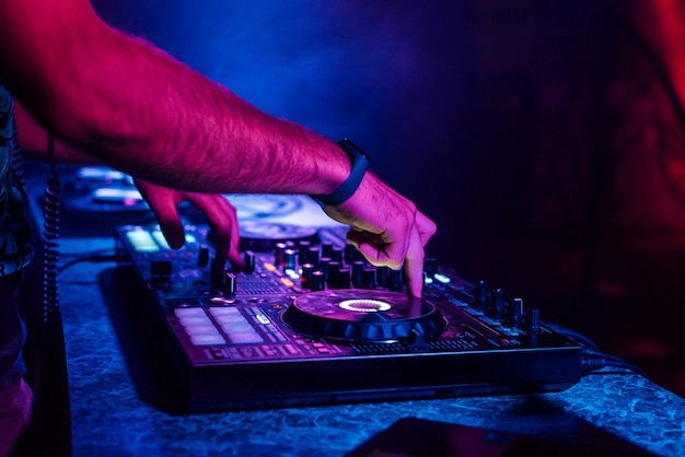 Hands of a dj playing music on a mixer at a concert