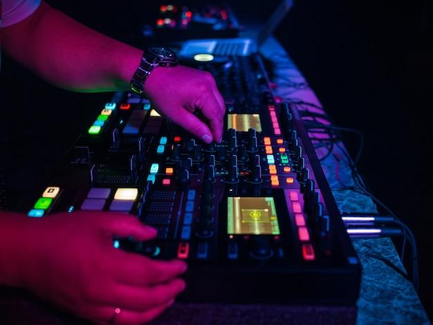 Hands dj микширует и играет музыку на профессиональном контроллере микшера