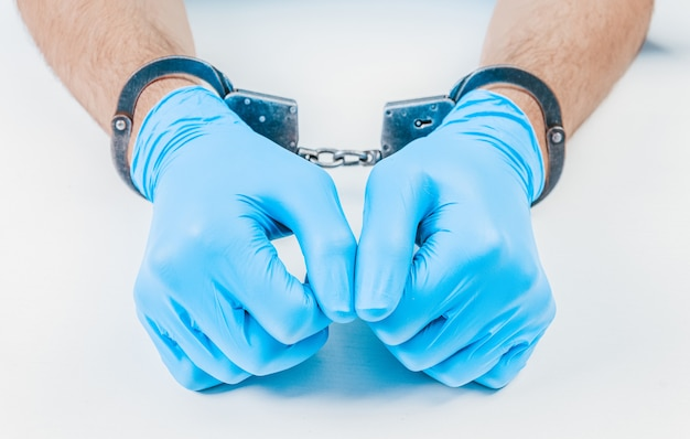 Hands of a doctor in handcuffs. the concept of corruption in medicine.