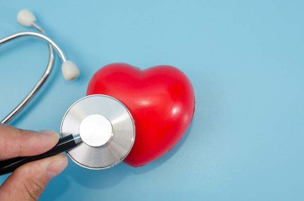 Hands of doctor with heart and stethoscope on blue