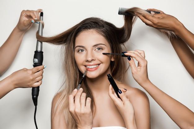 若い美しい女性のメイクと髪型をしている手