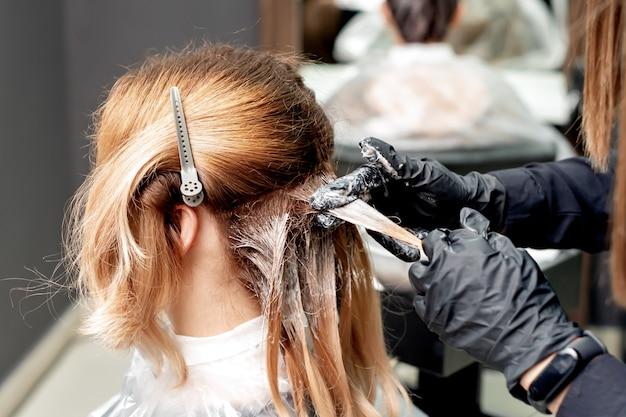 Руки красят волосы женщины