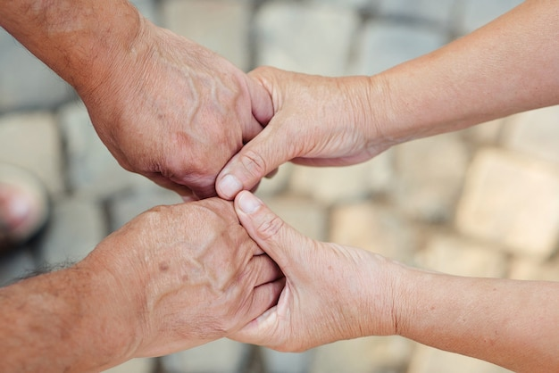 Hands of an elderly couple closeup olderly couple holding hands during walking love concept