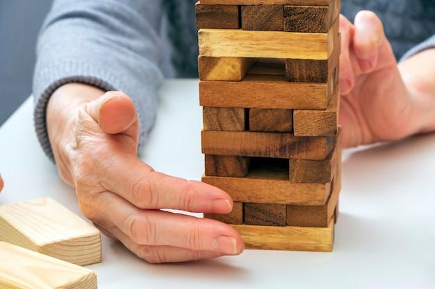 手高齢の女性は木製のブロックでボードゲームをプレイします。