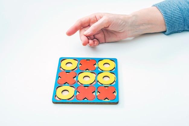 手高齢の女性の高齢者は三目並べの木製ボードゲームをプレイします