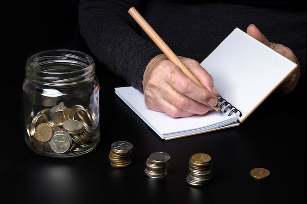 The hands of an elderly woman writing down their expenses in a notebook. a jar of small coins on a dark background.