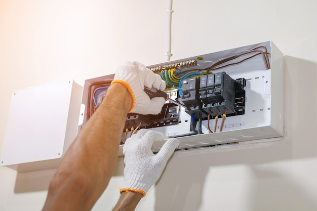 Hands of electrician using a screwdriver to tighten the circuit breaker.