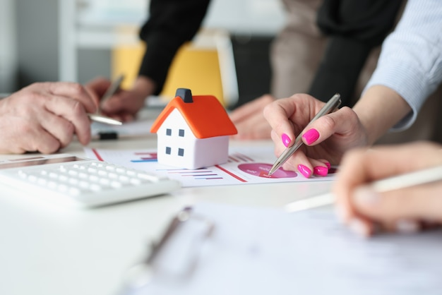 Hands of employees with pens and business charts and small house on table