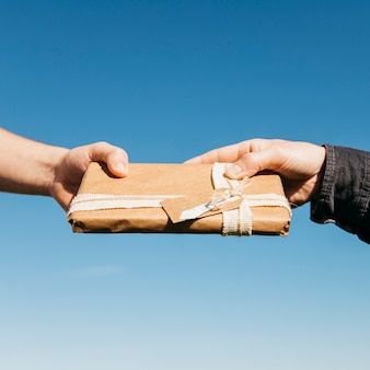 Hands exchanging present on sky background