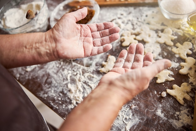 Hands of experienced baker being covered in flour