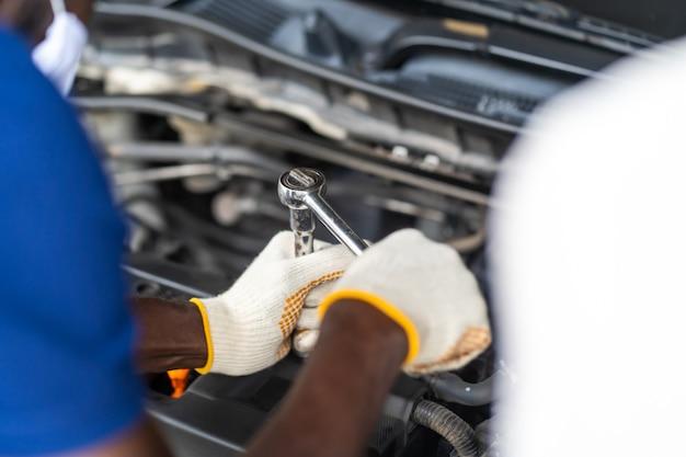 손 자동차 수리 서비스에서 전문 자동차 정비사. 자동차 정비 및 자동 서비스 차고 개념.
