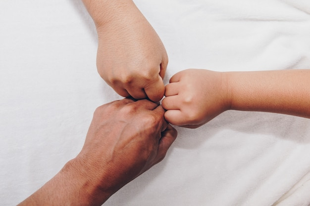 Hands of the family, a baby, a daughter, a mother and a father.