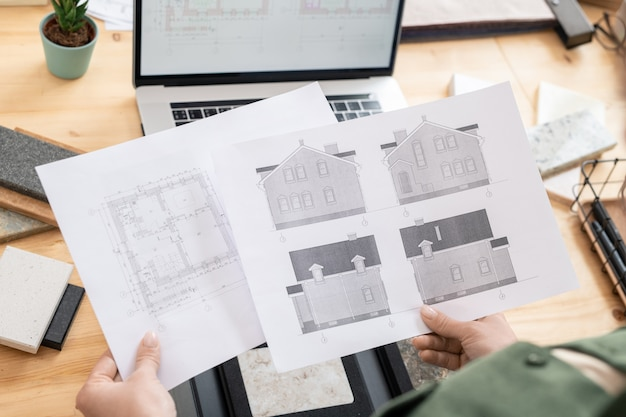 Hands of female architect holding papers with sketch of new house and its plan over table with laptop