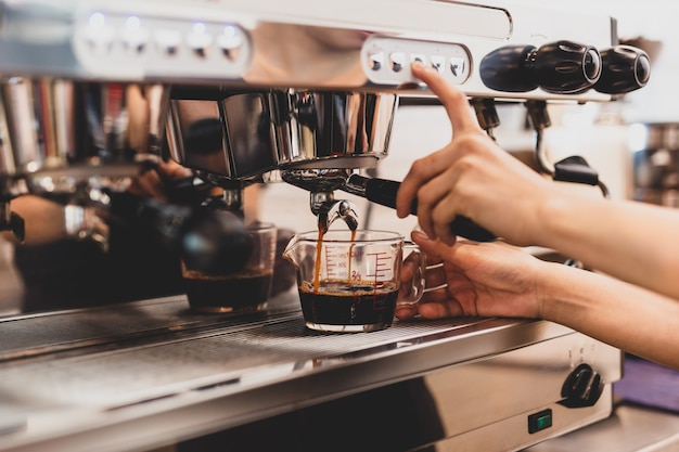 Hands of female barista pressing button on machine while making fresh coffee.