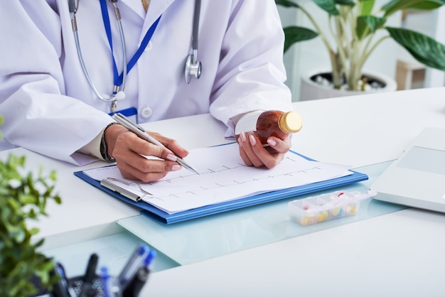 Hands of female doctor looking at cardiogram and holding bottle of medicine