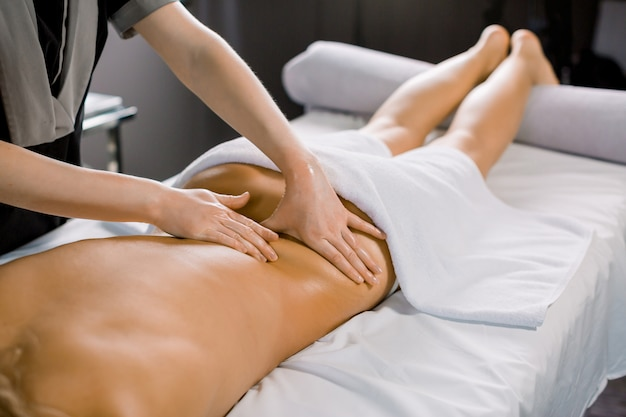 Hands of female masseur massaging back of woman client, lying on the couch in modern medical spa center
