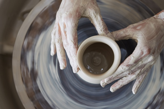 Hands of female potter sculpting clay vessel on spinning wheel