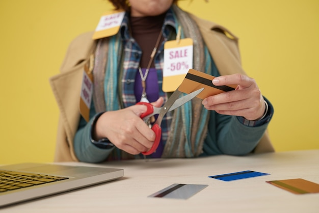 Hands of female shopaholic cutting her credit cards after buying too much clothes on sale