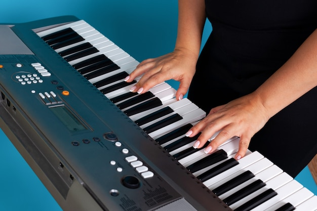 Hands and fingers of a woman playing an electronic synthesizer