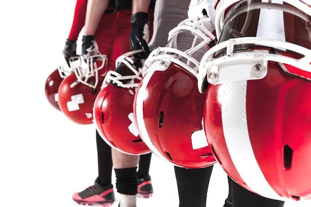 Le mani di cinque giocatori di football americano con caschi su sfondo bianco