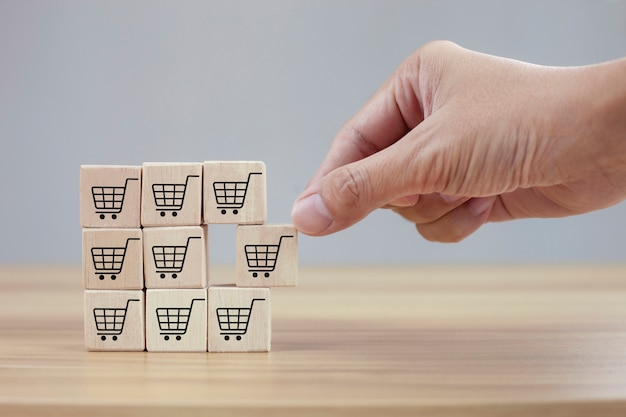 Hands flips cube with icon shopping cart symbol