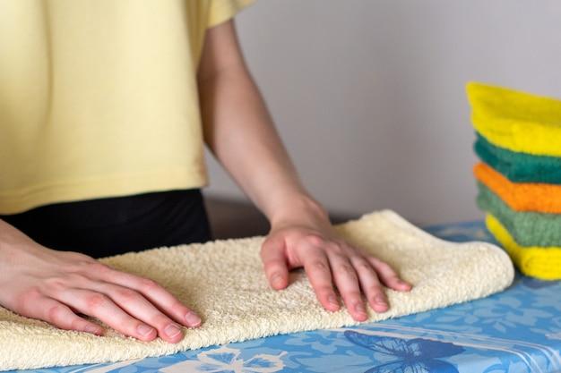 手はアイロンをかけたタオル、アイロンをかけたものの積み重ねを折ります。宿題のコンセプト、主婦。