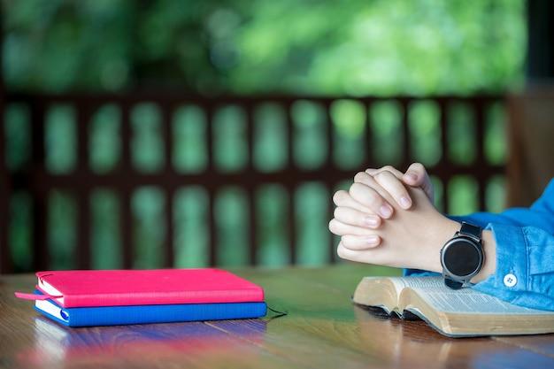 믿음, 영성, 종교를 위한 교회 개념에서 성경에 손을 접고 아침에 성경으로 기도하는 여성. 성경 기도와 함께 여자 손입니다.
