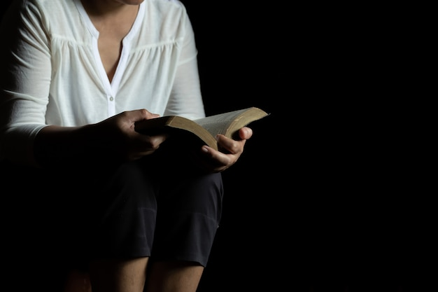 Hands folded in prayer holding a holy bible in church