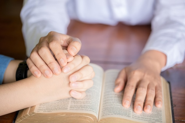 Hands folded in prayer on a holy bible in church concept for faith, spirituality and religion, woman praying on holy bible in the morning. woman hand with bible praying.