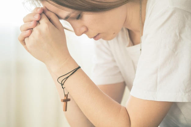 Hands folded in prayer on a holy bible in church concept for faith, spirituality and religion, woman praying on holy bible in the morning.