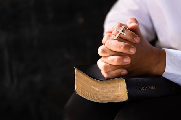 Hands folded in prayer on a holy bible in church concept for faith
