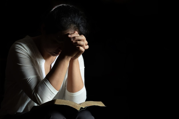 Hands folded in prayer on a holy bible in church