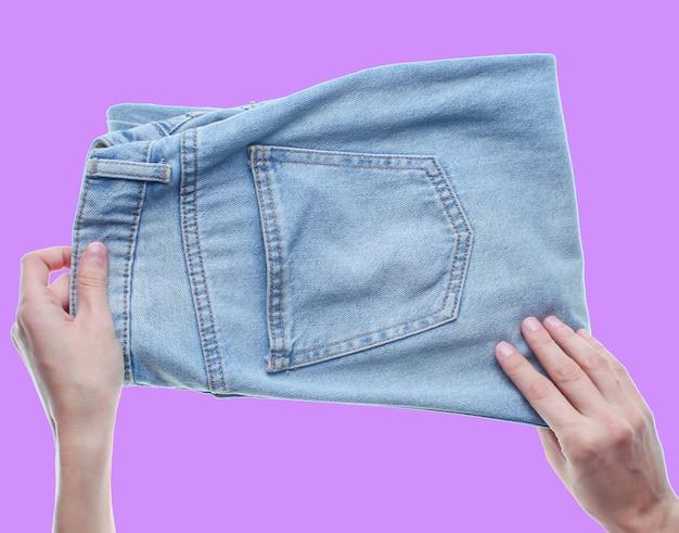 Руки складывая джинсы изолированные