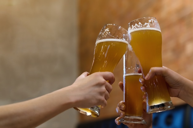Hands of friend clinking, cheering beer in cafe.