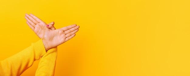Руки жест птицы над желтым