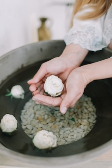 Hands of a girl holding flowers in a vintage sink with water