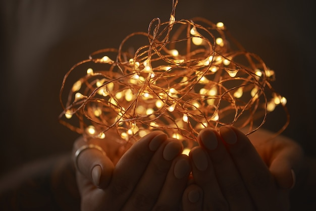 Hands of a girl holding a garland of christmas lights on a dark background