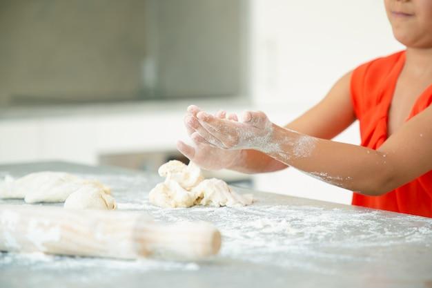 Mani della ragazza che impasta pasta sul tavolo della cucina con farina disordinata. kid cuocere panini o torte da sola. colpo medio. concetto di cucina familiare