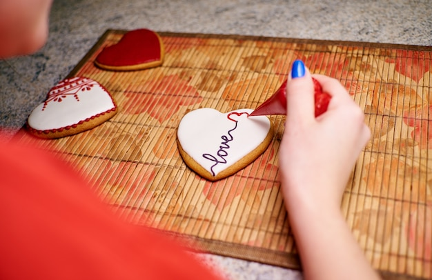 Hands of a girl paint homemade heart-shaped cookies with patterns