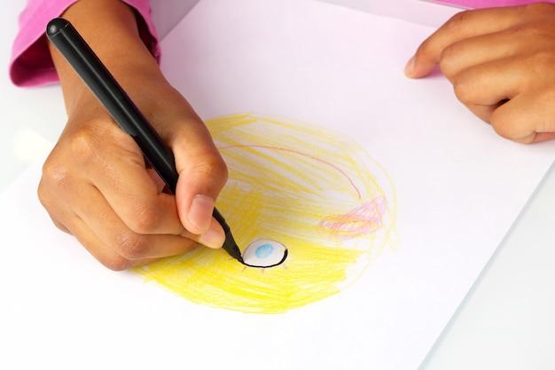 손 소녀는 만화의 얼굴을 종이에 그립니다.