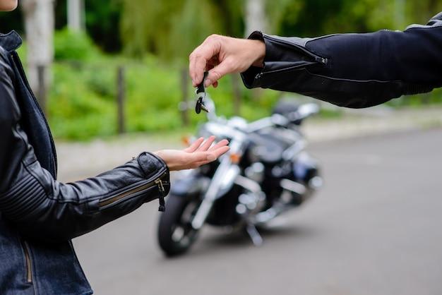 Руки отдают ключи от мотоцикла. концепция продажи и аренды мотоциклов.