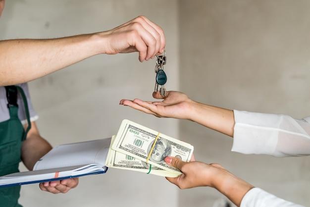 아파트에서 열쇠를 주고 받는 손, 근접 촬영