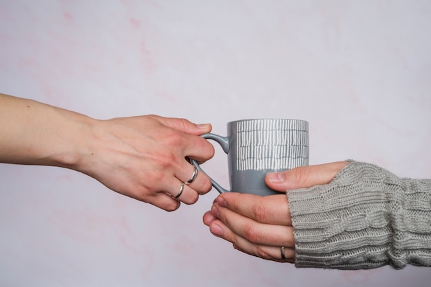 Hands giving cup to person in sweater