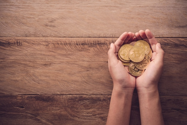 Hands giving gold coin on wooden floor - concept help for business
