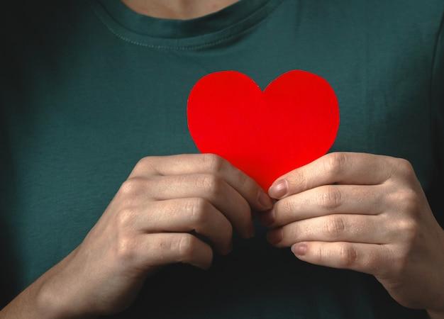 Руки дарят любовь и держат красное сердце. юн женщина держит бумажное сердце близко к телу. страхование жизни, всемирный день сердца и разума фото