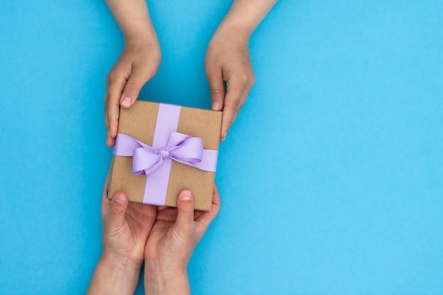 파란색 테이블에 라일락 리본이 달린 공예 종이에 선물을 주거나받는 손