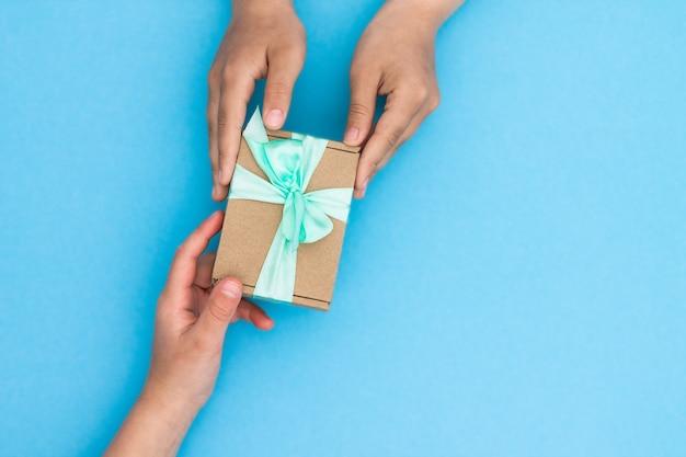 青にミントリボンが付いたクラフト紙でギフトを贈ったり受け取ったりする手