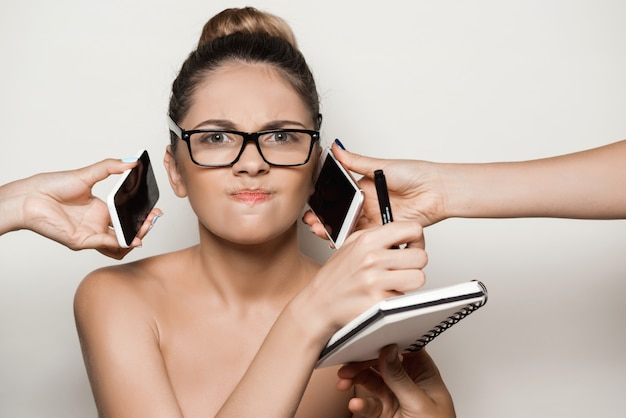 Hands giving phones to young beautiful businesswoman holding notebook