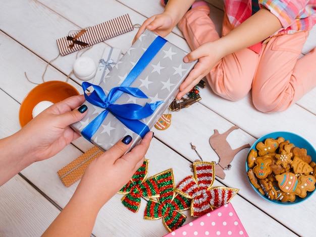 선물 상자를주는 손. 딸과 함께 선물을 공유하는 어머니